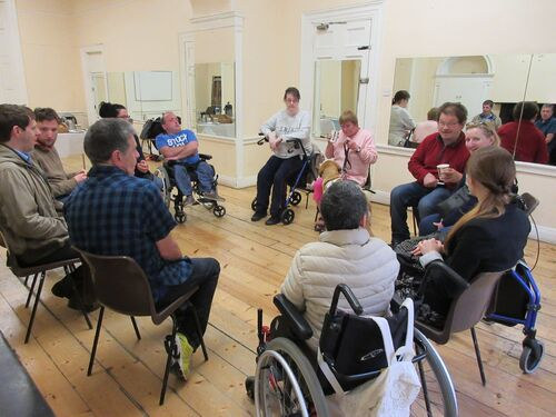 A group of people with disabilities sitting in a circle having a discussion