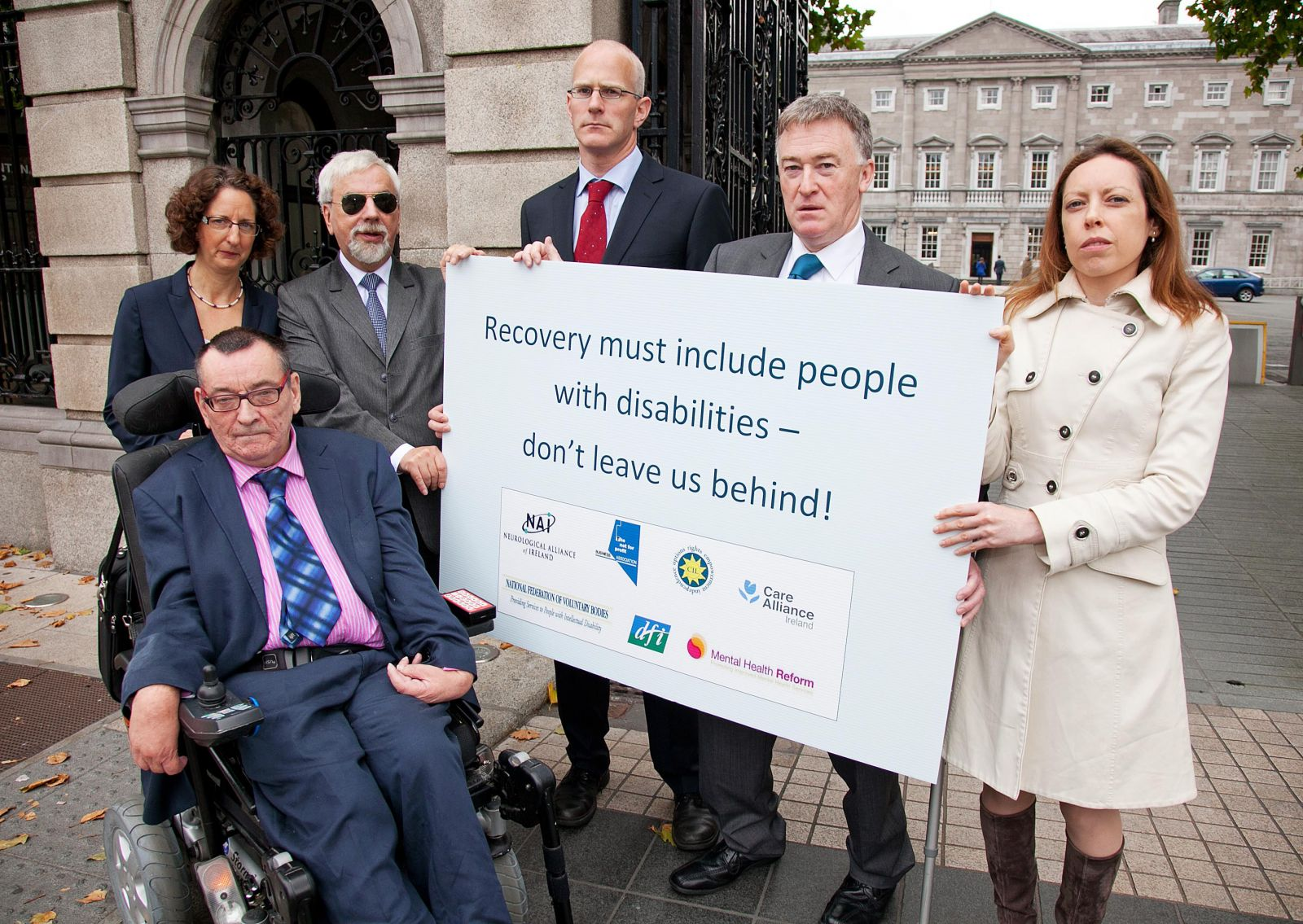 Sign stating: Recovery must include people with disabilities - don't leave us behind: held by Michael McCabe: Center for Independent Living, Shari McDaid : Mental Health Reform, Des Kenny : Not for Profit Business Association, Liam O'Sullivan : Care Alliance Ireland, John Dolan : Disability Federation of Ireland, Mags Rogers : Neurological Alliance of Ireland